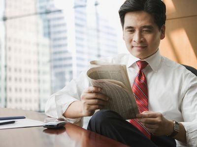 Person in tie reading newspaper