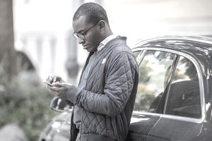 person with glasses in jacket leaning on car while using their cellphone