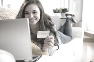 Girl shopping on sofa - stock photo