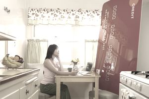 A woman looks at a huge credit card in her kitchen
