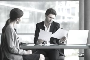 Man looking over papers at desk in front of woman