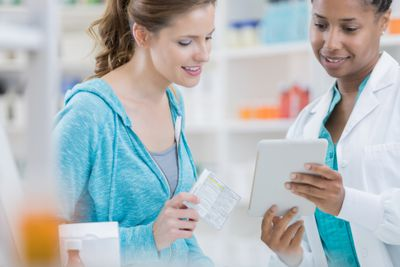 Professional pharmacist using digital tablet to assist customer in pharmacy