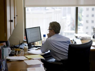Rear view of a thoughtful man sitting at a desk with laptop in front of a window showing a city skyline