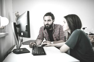 Young freelancing couple looks at computer in home office