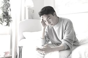 distressed man sitting on bed
