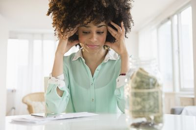 Woman sitting down to pay her bills with a jar of money in front of her