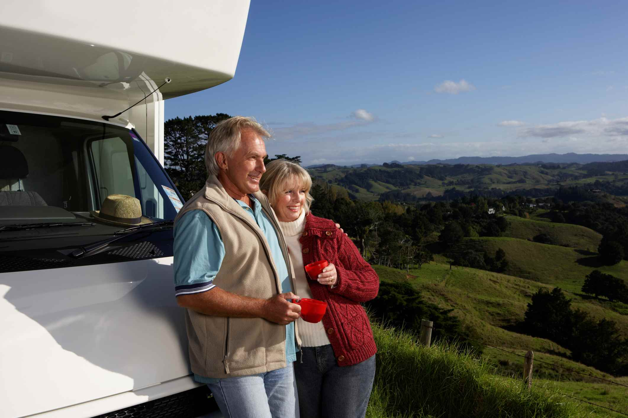An older couple standing by an RV