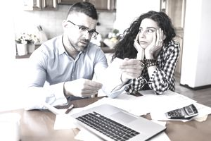 young couple looking at documents together at kitchen table