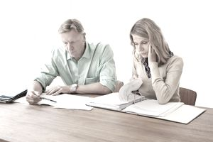 a man and woman sitting at table going through paperwork together
