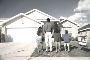 Rear view of family looking at house for sale