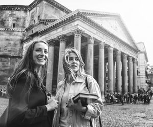 Two Young Women Standing in Front of Historic Building, One Holds a Book