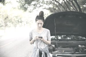 Young woman on cellphone near car with open hood