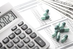 Image of desktop calculator and a spreadsheet printout with medicinal capsules on top to indicate Research and Development as an operating expense on the income statement of a pharmaceutical company