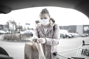 Young woman with face mask outdoors putting shopping bags in car.