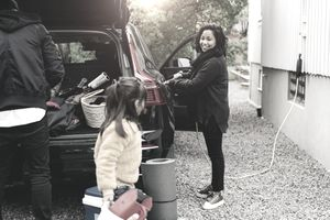 woman charging her car while her family packs it with things