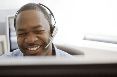 Smiling customer service rep wearing headset looks at computer