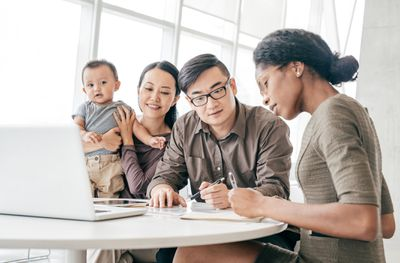 Young couple with toddler sitting at a desk with accountant