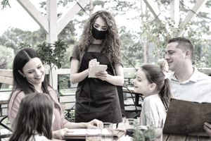 Waitress with face mask serving family with children outdoors in summer on terrace restaurant