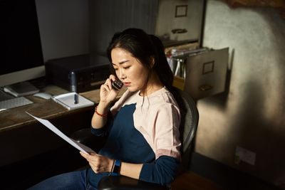 Worried woman at a desk, reading paperwork while on the phone.
