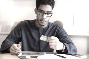 businessman using credit card and digital tablet at office.