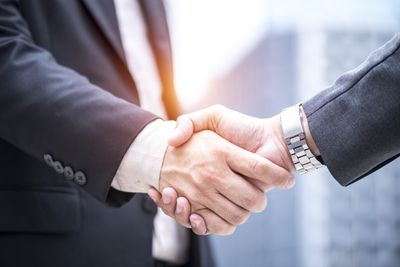 Two businessmen shaking hands after forming a limited partnership