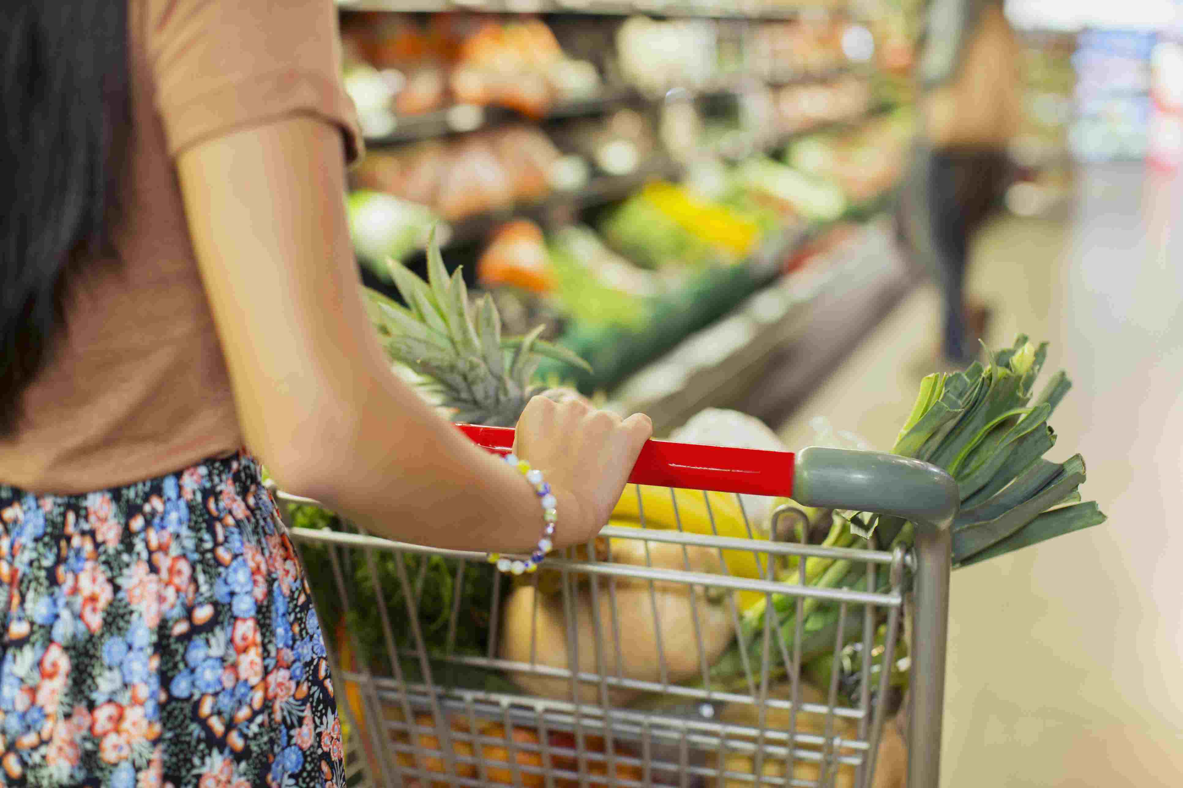 Close-up of woman pushing full shopping cart in grocery store