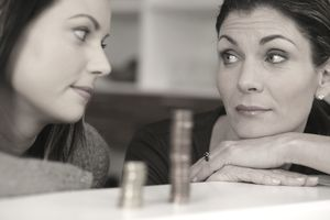 Two women staring at each other in front of a stack of coins