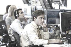 A person on the trading desk stares at a computer monitor
