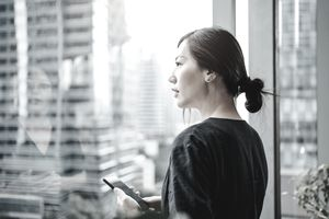 Young urban businesswoman using smartphone in the office in front of windows overlooking the city