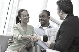 Couple shaking hands with a businessman