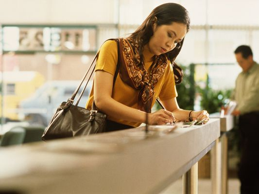 woman filling out form at bank counter