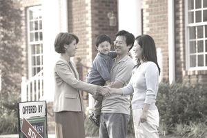 Asian family shaking hands with real estate agent next to house