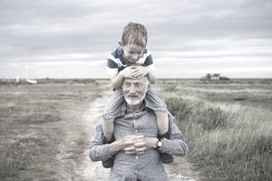 A grandfather and his grandson enjoy a day out in nature