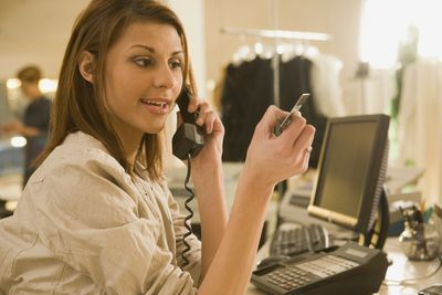 Woman on phone in shop, looking at a credit card.