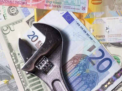 pile of foreign currency with wrench on top