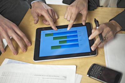Hands around digital tablet showing financial graph