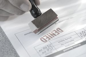 "Man's hand stamping ""denied"" on mortgage application"