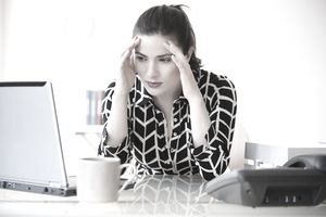 businesswoman with headache using laptop