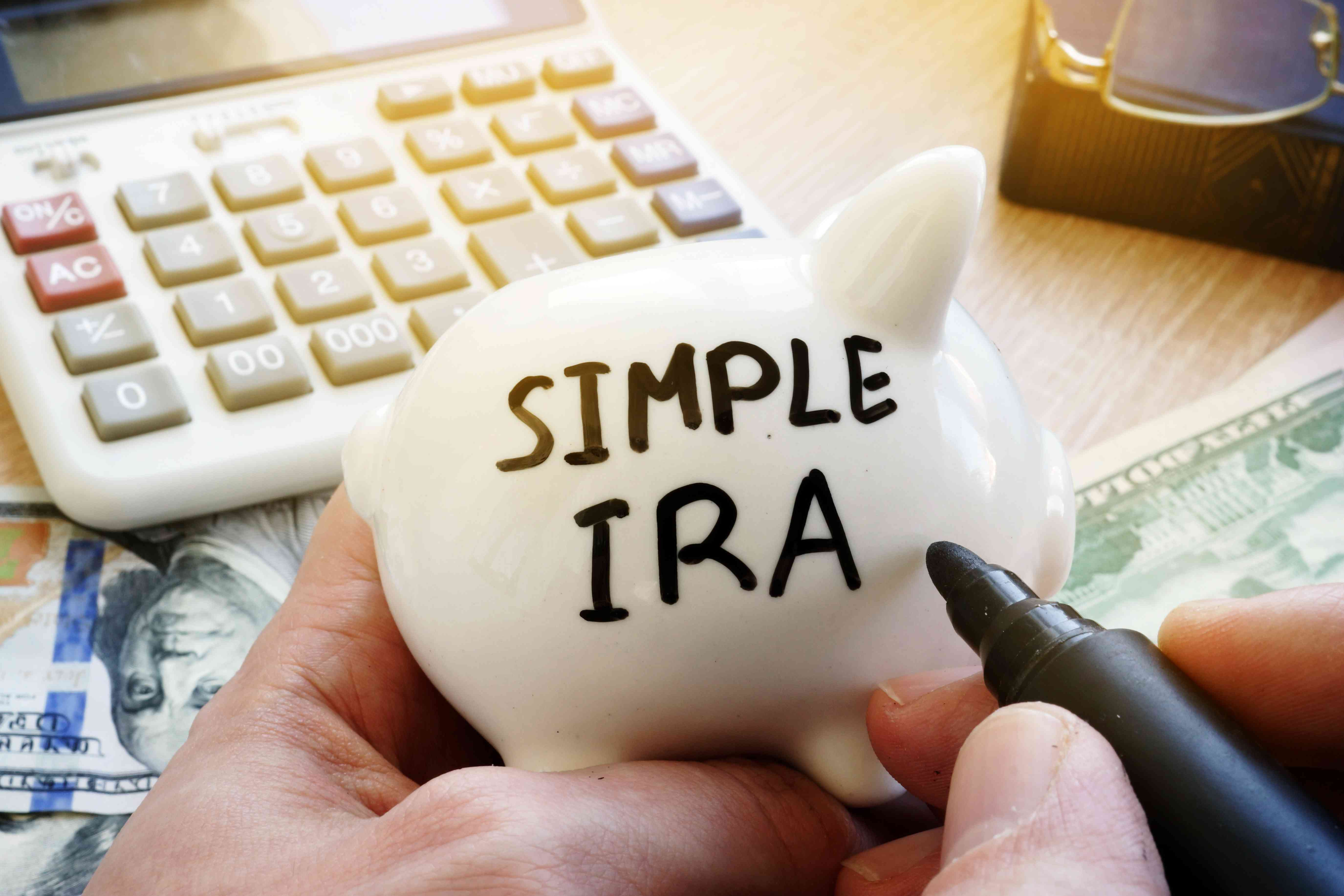 Calculator, money, and piggy bank with Simple IRA written on it