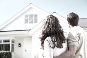 Couple facing away from camera standing in front of house