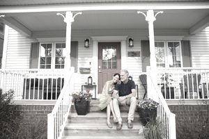 On older couple relaxes on the porch of an adorable, clapboard-sided home.