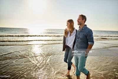 Couple strolling on a beach at sunset
