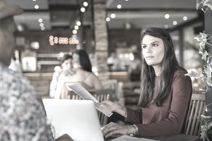Women seated at restaurant table with laptop and papers gazing at man seated before her