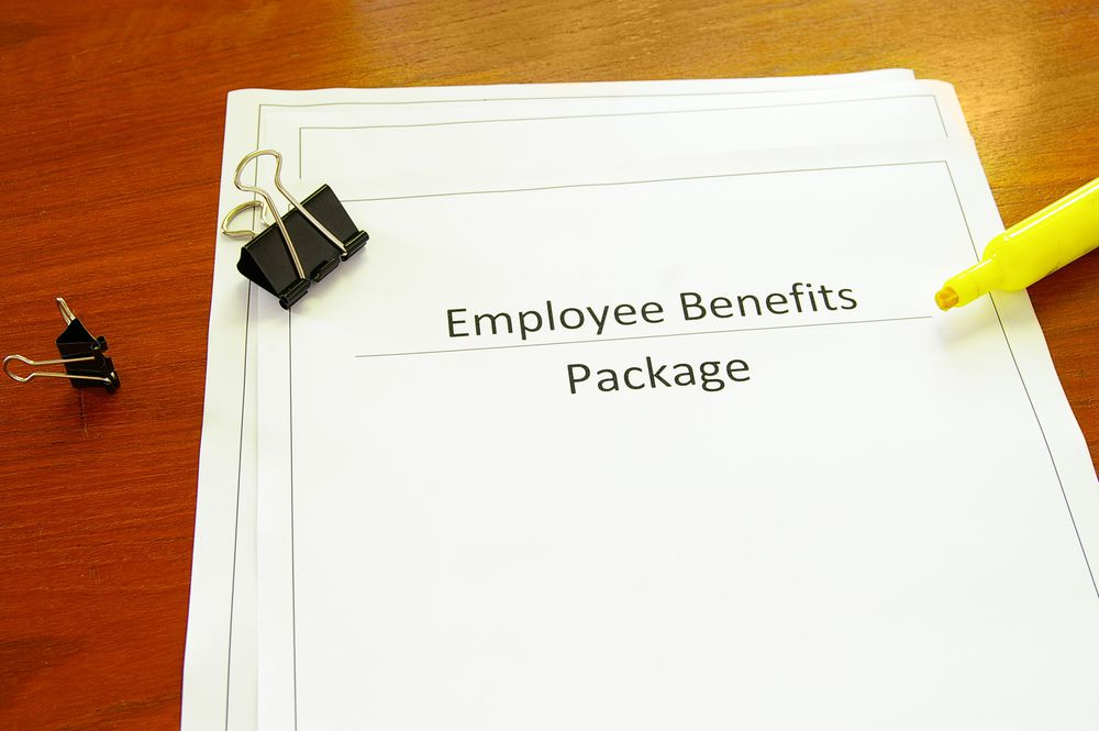 Employee Benefits Package lays on a table top with a highlighter pen and paper clips