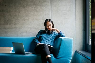 Student seated on blue sofa with laptop researching scholarships for college