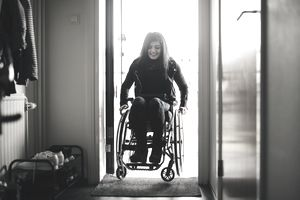 Smiling young woman using a wheelchair as she moves through an assessable doorway