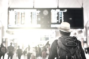 A backpacking flyer steps into the crowded terminal confident the perks provided by his airline credit card will see him comfortably to his destination.