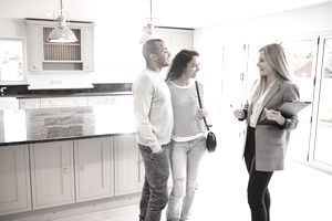 Realtor showing house for sale to a young couple.