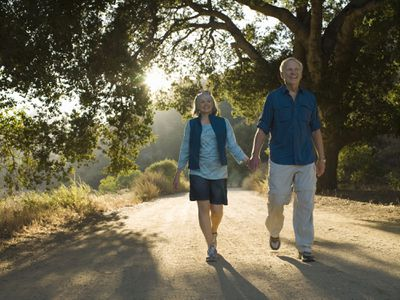 Smiling retired couple with enough savings in the bank taking a sun-filled walk in the park