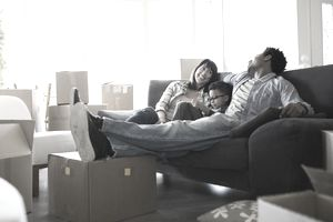 A family sitting on a couch surrounded by moving boxes